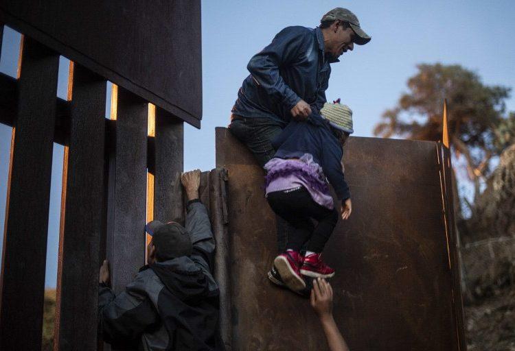 """Familias de migrantes centroamericanos se arriesgan a escalar el muro a los EE. UU. en busca del """"sueño americano"""""""