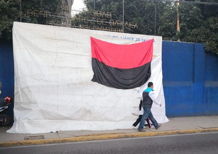 Cuelgan banderas rojinegras en la UABJO