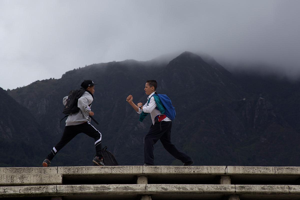 Martín juega con un amigo en la calle, al fondo una gran montaña con árboles y niebla
