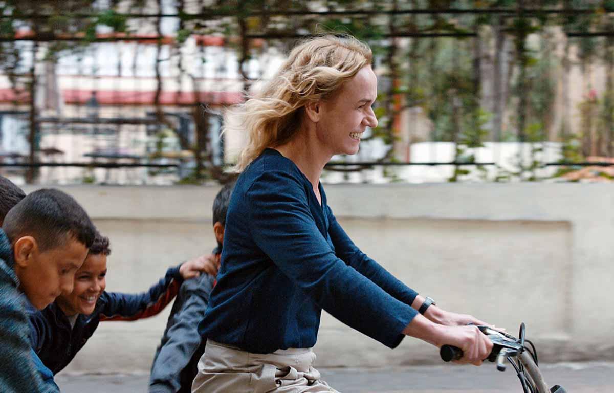 Edith en bicicleta está feliz disfrutando la vida en Marruecos. Dos niños la persiguen mientras ella anda en bicicleta