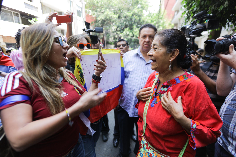 Una mujer joven mira de frente a una mujer mayor y ambas gritan sus consignas fuera de la embajada de Venezuela.