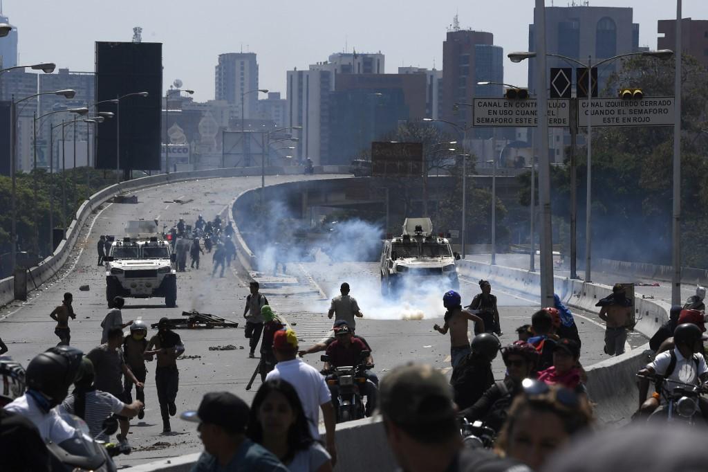 Personas y militares en las calles de Caracas se enfrentan