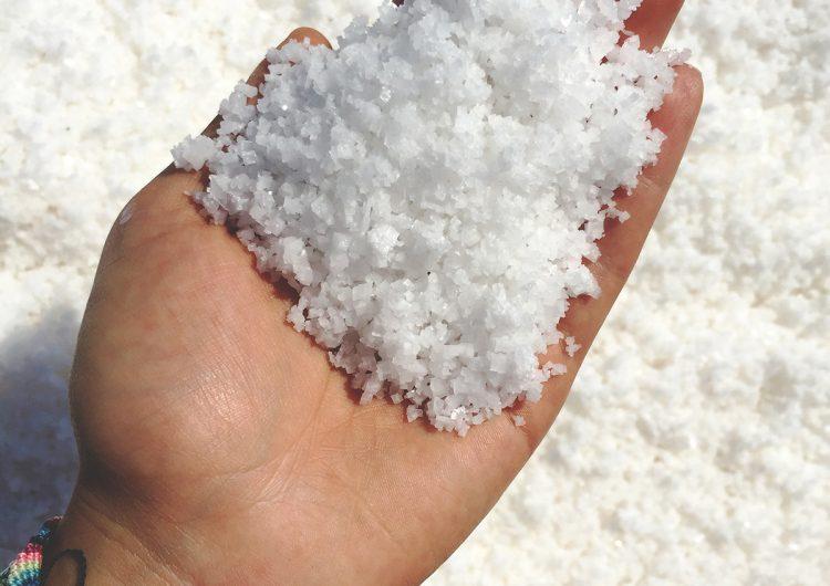 La mano de una mujer nos muestra los granos de la sal de Colima.