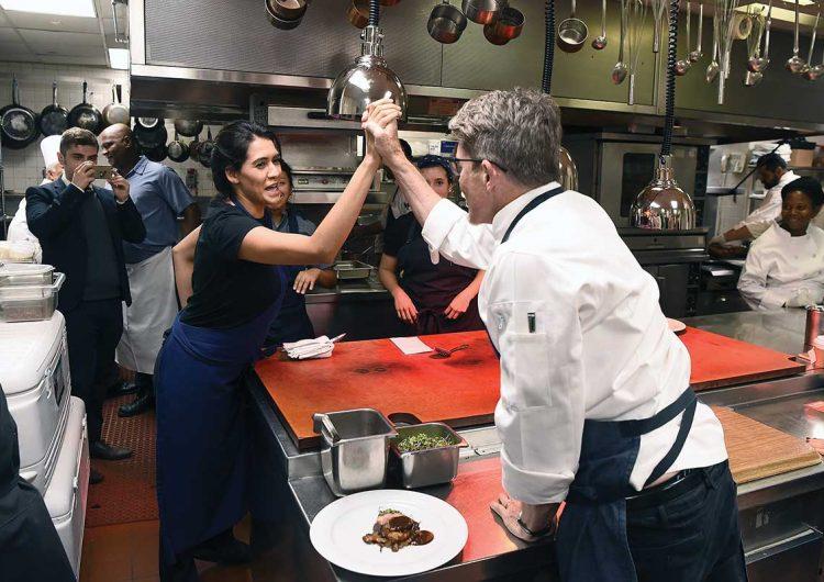la chef choca manos con un chef en la cocina en señal de triunfo