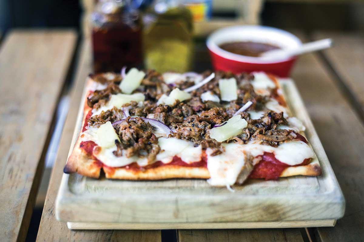 En la foto se ve una pizza, la cual también forma parte e los antojitos del lugar.