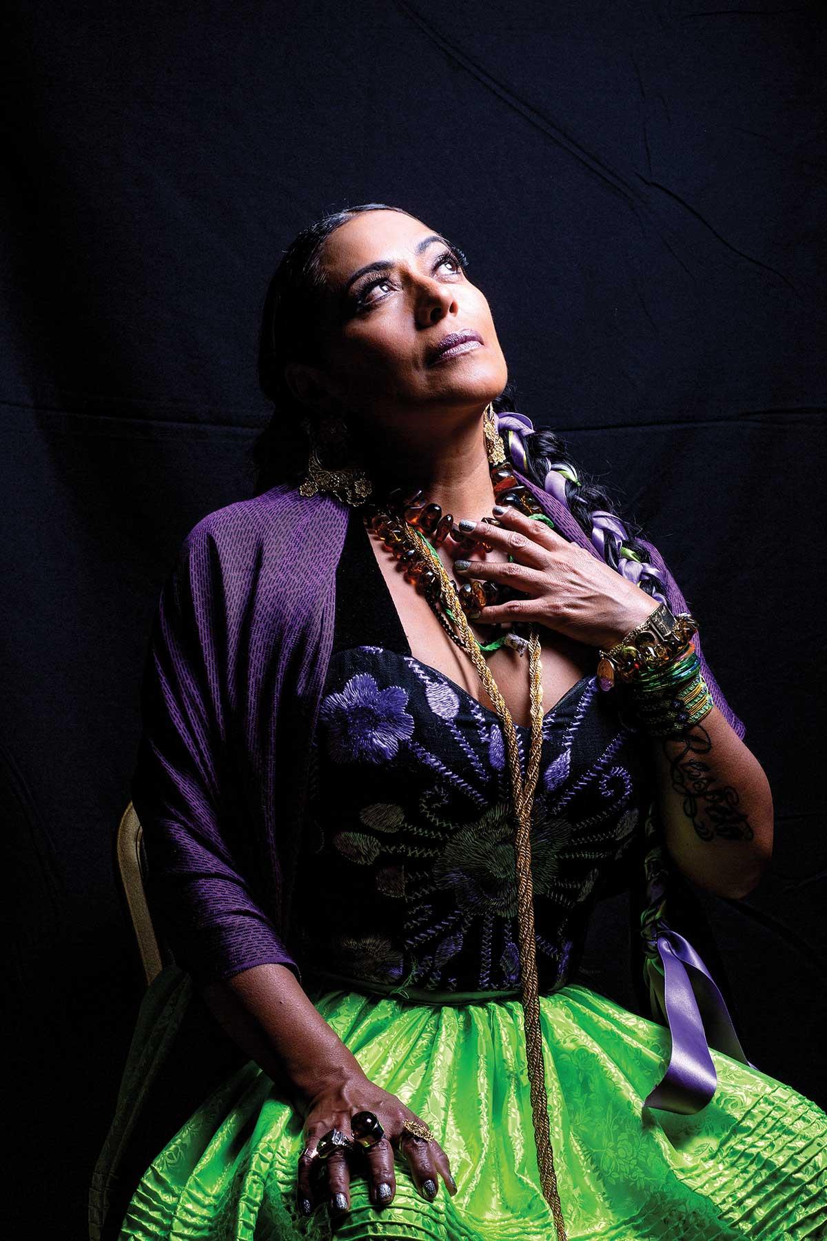 Lila Downs, la cantante, posa mirando al cielo con una blusa tipo corset y un chal morado y una falda verde de seda.trae collares y muchas pulseras.