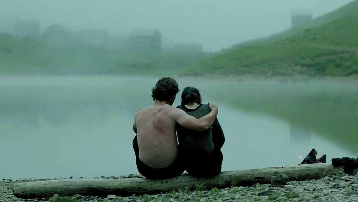Sentados de espaldas, un hombre pasa su brazo sobre el hombro de una mujer. Una foto en la niebla y el campo.