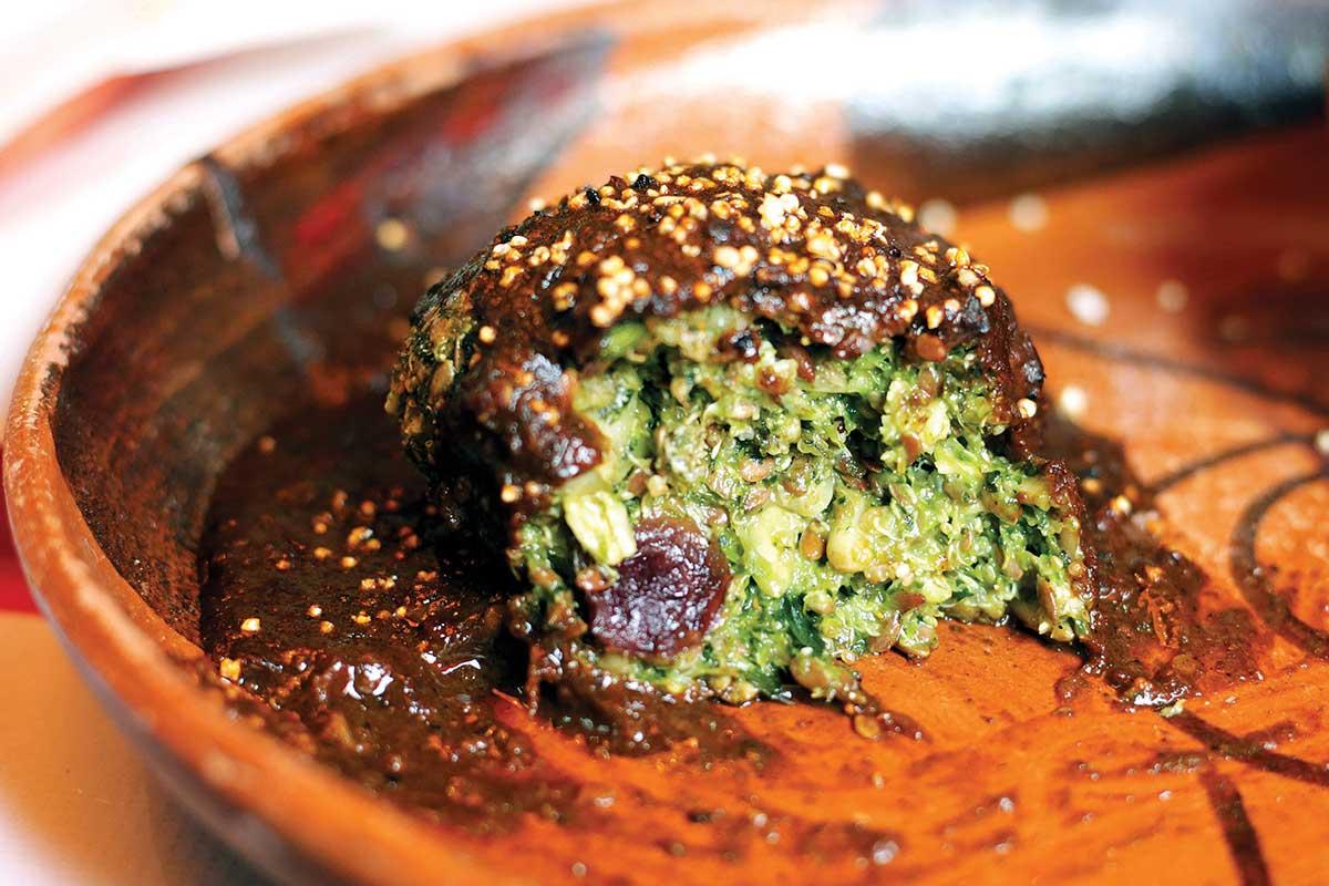 En la foto se observa una tortita de verduras que se guisaba desde tiempos prehispánicos. Está bañada en mole.