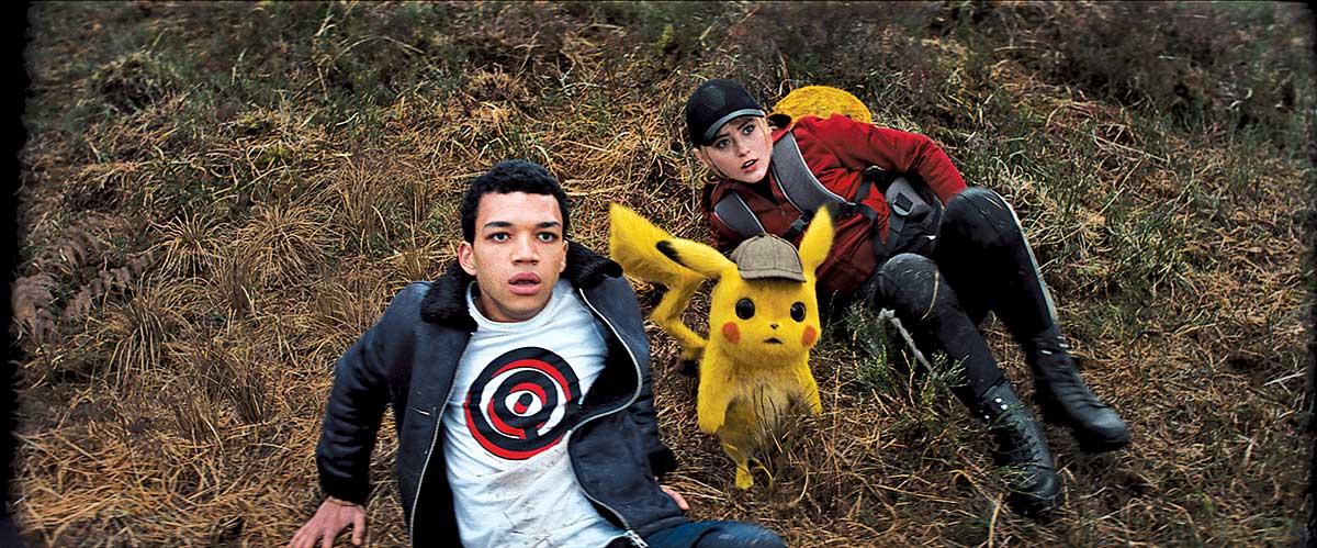 un joven y una jovencita están tirados en el pasto con cara de susto en medio de ellos Pikachú