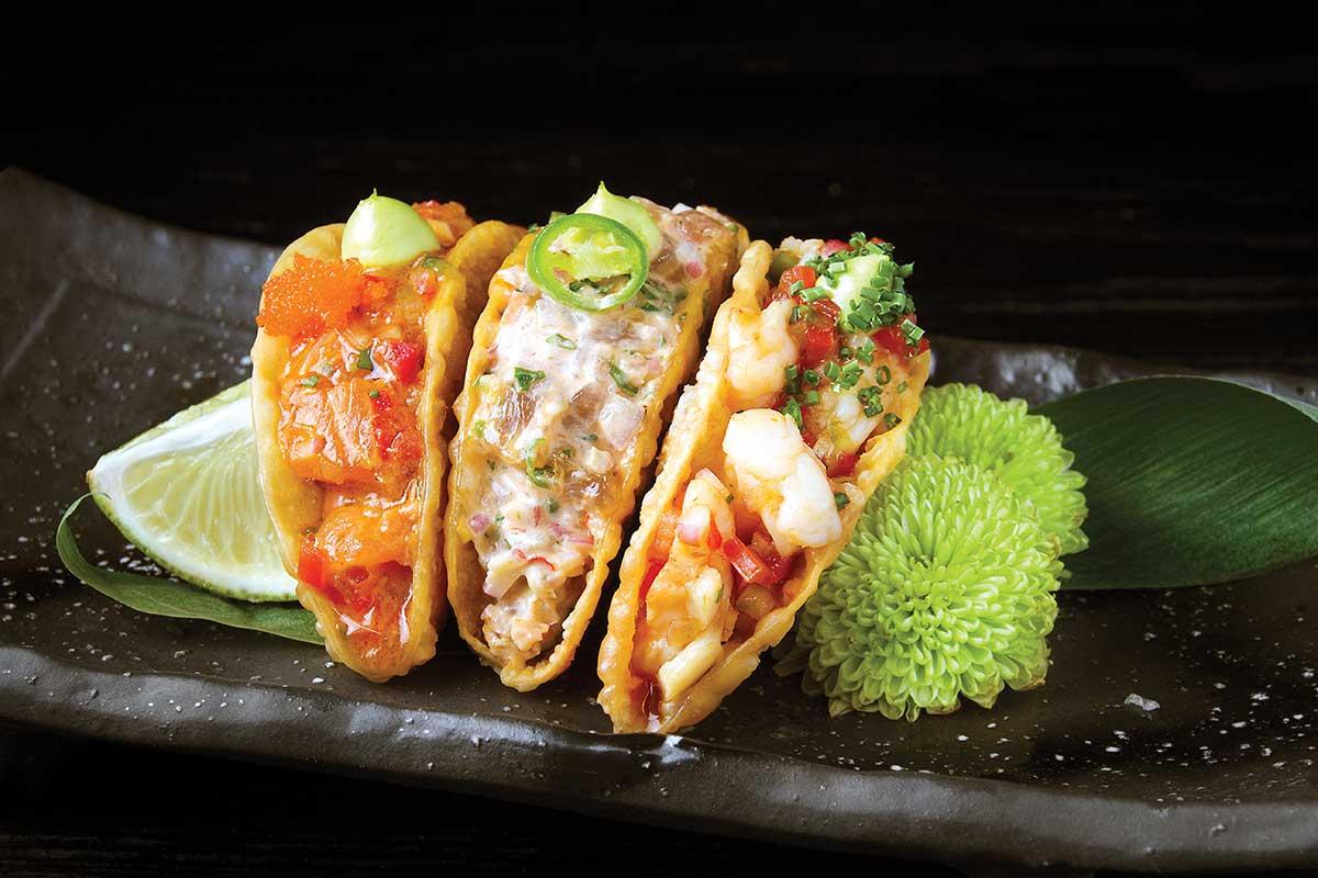 en la foto se observan tacos de camarón y mariscos como si fuera sushi en taco.
