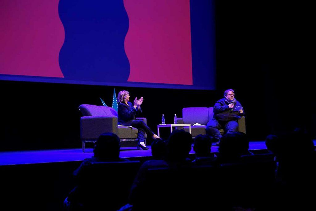 sentados en unos sofás y con micrófono en mano, Melissa Cobb y Guillermo del Toro platican con el público.