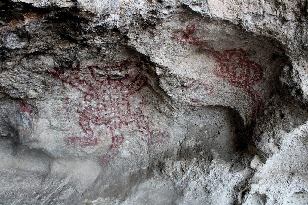 En un acercamiento a una de las cuevas se ve una pintura rupestre de un tigre hecha con una tintura roja