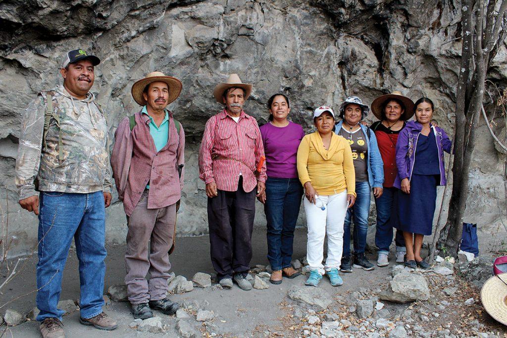 Un grupo de ejidatarios posan para una foto. Están dentro de la cueva con pinturas rupestres.