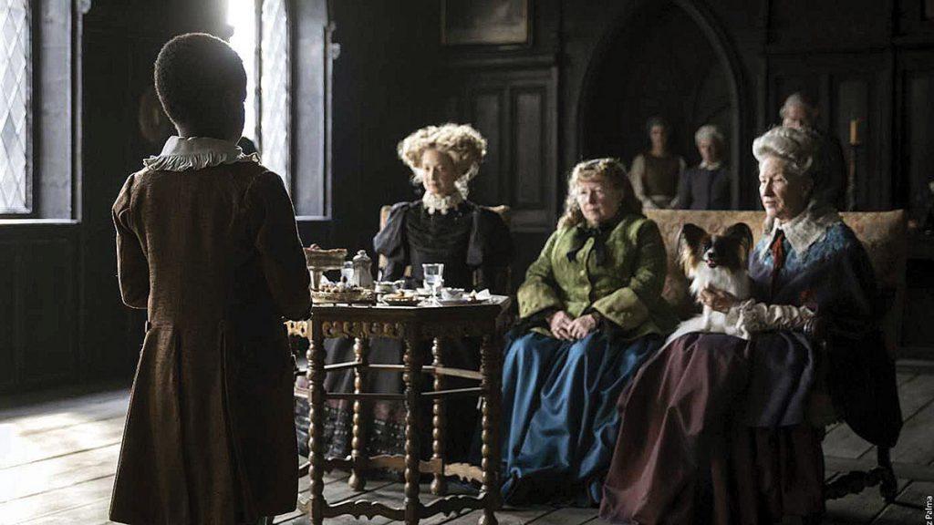 Se ve de espaldas a un joven negro vestido con ropas medievales color dorado. De frente unas mujeres de vestidos largos lo escuchan.