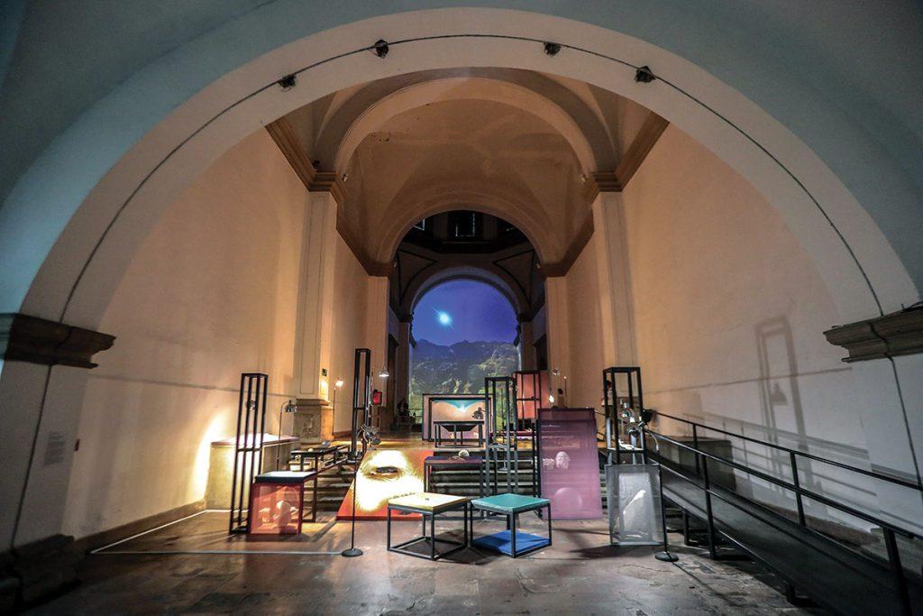 una bóveda como de un convento y, dentro de ella, cuadros, relojes, libreros, máquinas