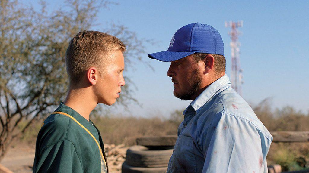 un joven y un hombre se miran de frente al fondo se ve un paisaje de campo.