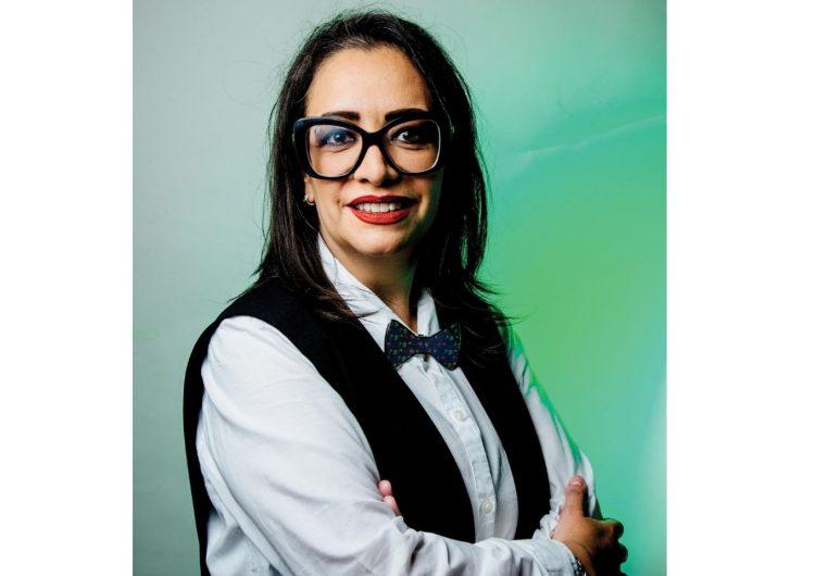 Hilda en close up posa con los brazos cruzados y una corbata de moño y sus grandes lentes negros