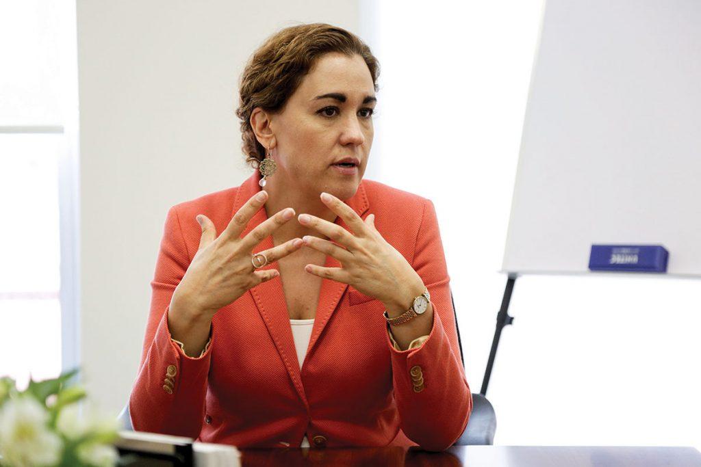 Mariana Ortiz habla en su oficina, mueve las manos y trae un saco color salmón