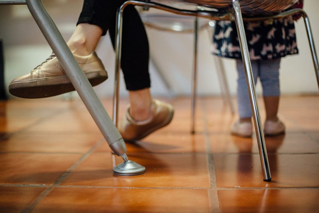 En la foto se ven solo las piernas de una mamá y una niña. Es una foto tomada desde debajo de una mesa.