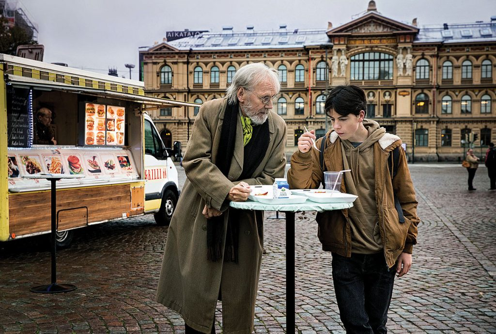 un adulto mayor y un joven conversan recargados en una mesa en medio de una plaza. Al fondo un edificio medieval.