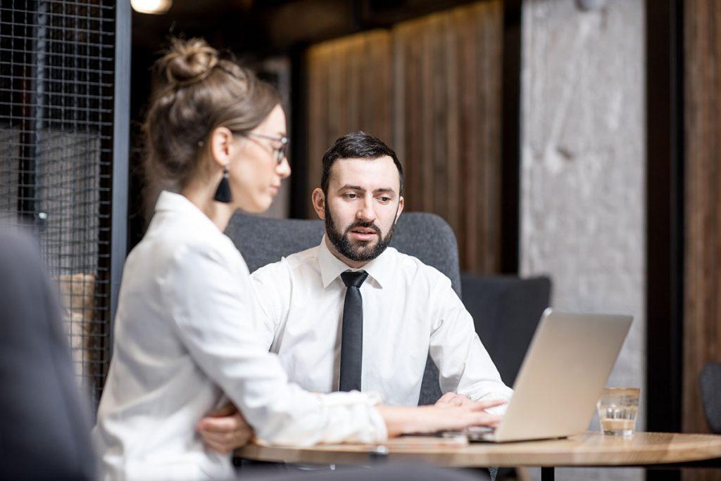 un colega hombre y una mujer trabajan juntos sentados frente a una computadora