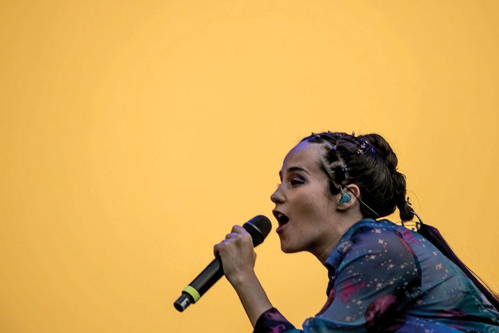 en un escenario de fondo amarillo la cantante Ximena Sariñana interpreta sus últimas canciones. Es un close up de ella de perfil.