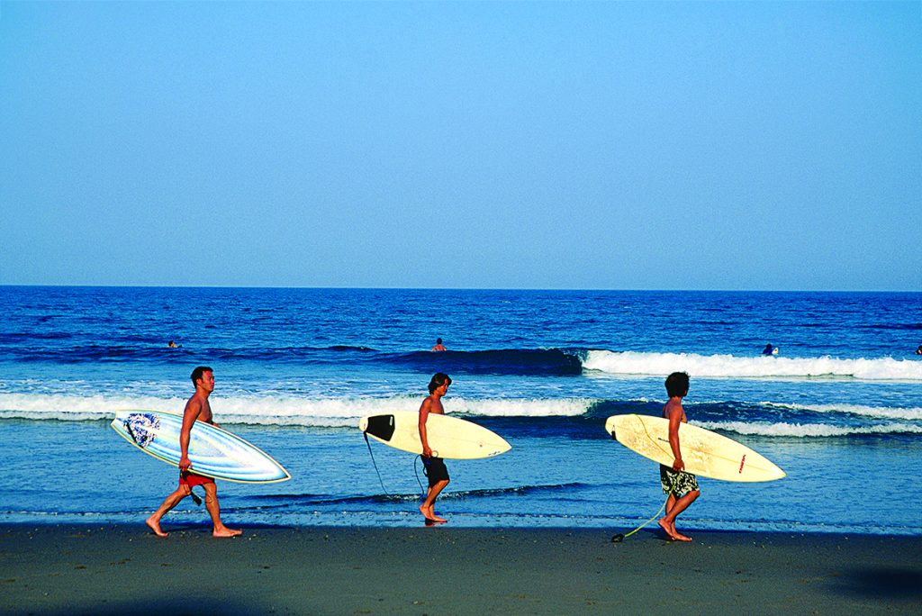 Three surfers carrying boards along Hirano Beach near mouth of Shimanto River.
