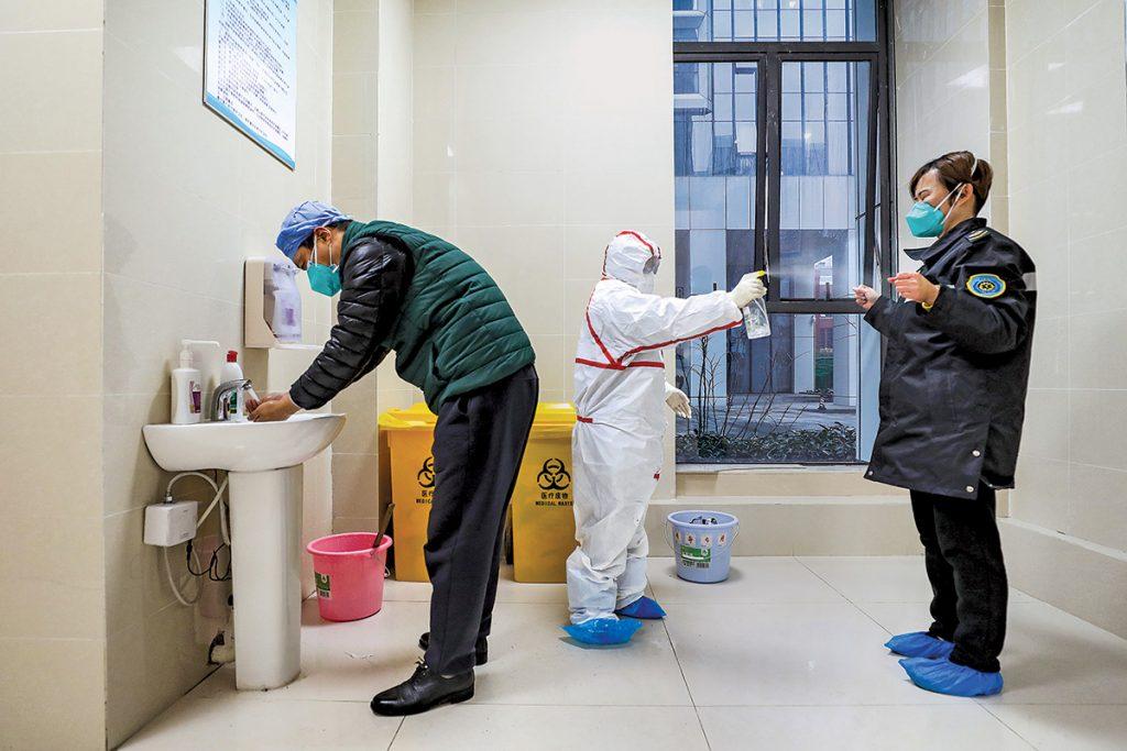 Trabajadores de salud desinfectan al personal de una ambulancia en un hospital en Wuhan. Foto: Feature China/Barcroft Media/Getty