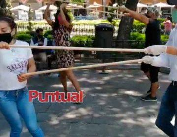 Practican pasos de baile con sana distancia en el zócalo de Puebla
